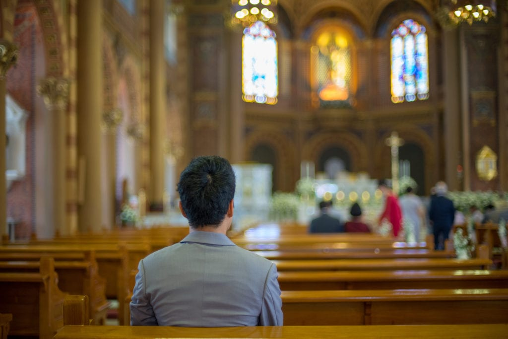 back of man's head sitting in church pews