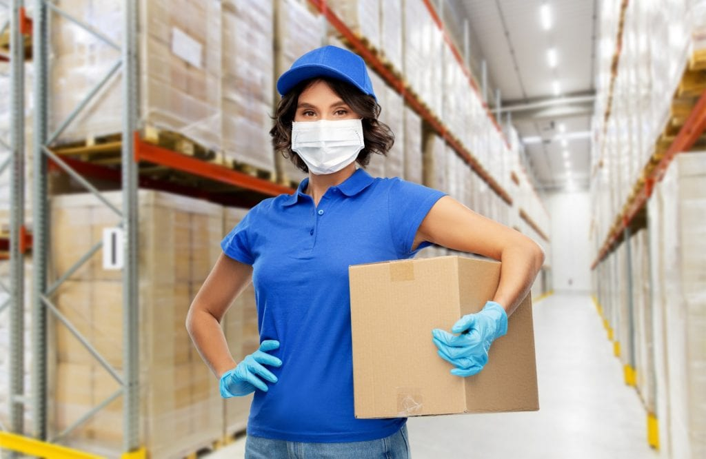 female warehouse worker wearing face mask and gloves as coronavirus protection