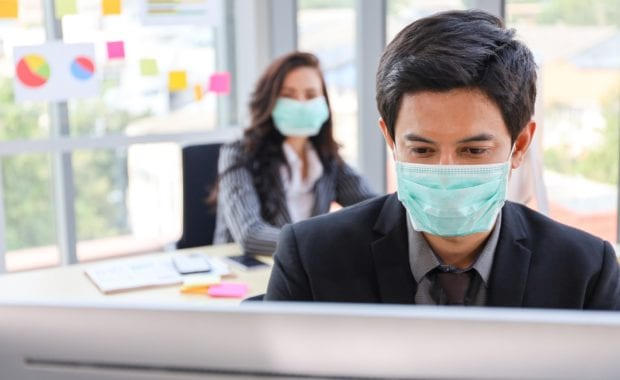 man and woman at desks in and office wearing facemasks