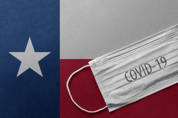 facemask with covid-19 on it on a texas state flag