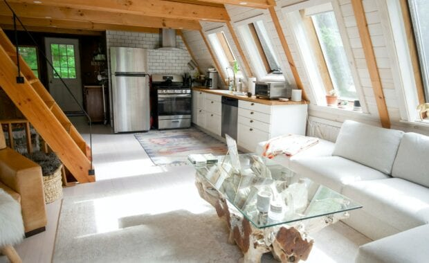 tiny house living room of an air bnb with a small kitchen and white sofa
