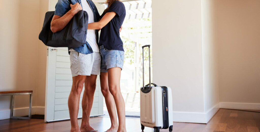 young couple with suitcases in a vacation rental home